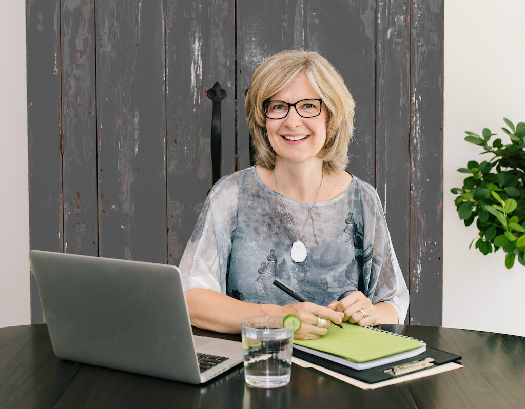 Nel Slater, Career and Life Coach, sitting in front of her laptop at her desk.
