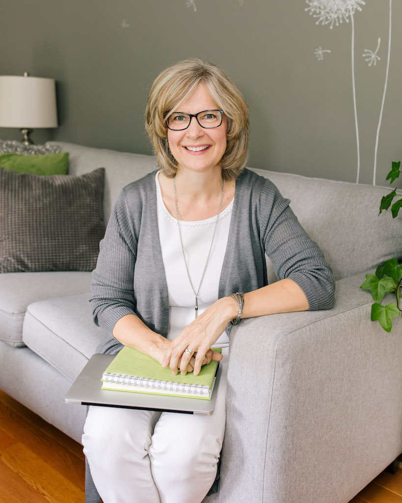 Nel Slater, Career & Life Coach sitting a note book and laptop on a grey couch.