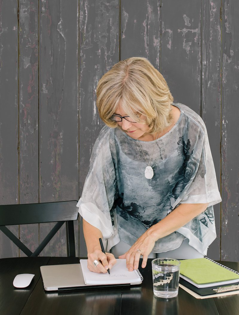 Nel Slater, Career and Life Coach, writing on a notepad on her desk